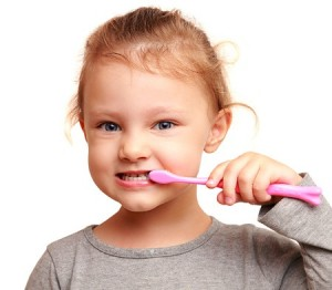 child brushing teeth after eating holiday treats